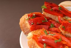 Side view of roasted red peppe. R and basil bruschetta on a white plate Stock Images