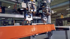 A side view on a robotic steel processing machine with changing tool heads. A new set of tool heads lowers down to work on a stainless steel box stock video