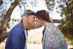 Side view of romantic couple sitting on tree trunk Royalty Free Stock Photography