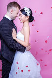 Side view of romantic wedding couple embracing against pink background Royalty Free Stock Image