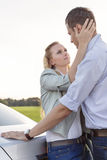 Side view of romantic young couple by car at countryside Royalty Free Stock Photo