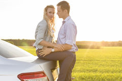 Side view of romantic young couple by car at countryside Stock Photography