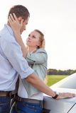 Side view of romantic young couple by car at countryside Royalty Free Stock Image