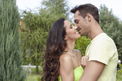 Side view of romantic young couple kissing in park Royalty Free Stock Photos