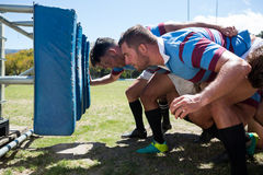 Side view of rugby players crouching at field Royalty Free Stock Photo