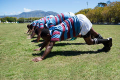 Side view of rugby players exercising at grassy field Stock Images