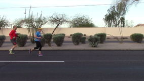 Side view of runners participating in a marathon stock footage