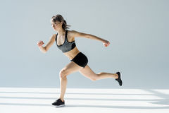 Side view of running woman in sportive clothing. On grey Stock Photos