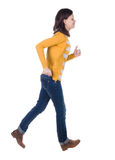 Side view of running  woman in yellow cardigan Royalty Free Stock Photography
