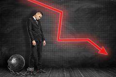Side view of sad businessman standing shackled to big metal ball and looking down near black graph-ruled wall with red stock photo