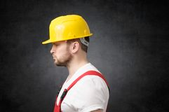 Frustrated construction worker. Side view of a sad construction worker with yellow hard hat Royalty Free Stock Photos
