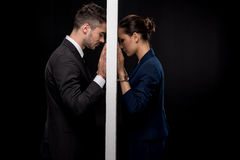 Side view of sad couple in formal wear separated by wall. Isolated on black royalty free stock images