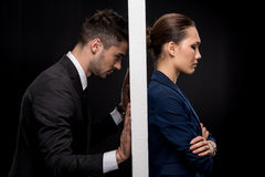 Side view of sad couple in formal wear separated by wall. Isolated on black royalty free stock photos