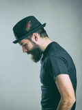 Side view of sad hunched bearded man with hat looking down. Royalty Free Stock Image