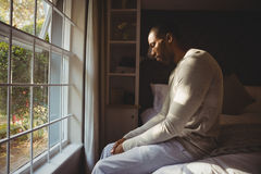Side view of sad man sitting on bed by window Royalty Free Stock Photography