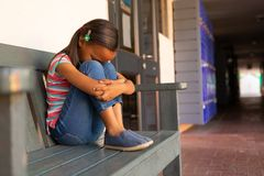 Sad schoolgirl sitting alone on the bench in the corridor. Side view of a sad mixed-race schoolgirl sitting alone on the bench in the corridor at school royalty free stock photo