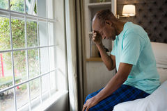 Side view of sad senior man sitting on bed by window at home. Side view of sad senior man sitting on bed by window in bedroom at home Royalty Free Stock Photography
