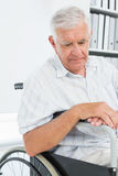 Side view of a sad senior man sitting in wheelchair Royalty Free Stock Images