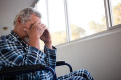 Side view of sad senior man sitting on wheelchair. In nursing home royalty free stock photos