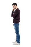 Side view of sad worried man in maroon pullover looking down. Full body length portrait isolated over white studio background Royalty Free Stock Image