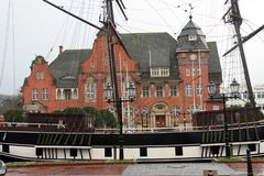 Side view on a sailor ship right in front of the civil hall in papenburg germany. And photographed with wide angle lens during a sightseeing tour in papenburg stock photo