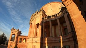 Side view of San Luca Sanctuary. Side view of facade of Sanctuary of Madonna di San Luca and arcades of its long portico with light of sunset. The church of stock video