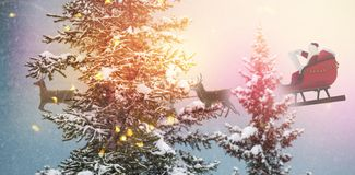 Composite image of side view of santa claus riding on sleigh during christmas. Side view of Santa Claus riding on sleigh during Christmas against snow covered Royalty Free Stock Image