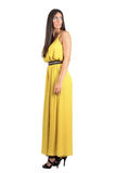 Side view of scared fashion model in yellow evening dress looking behind over her shoulder Royalty Free Stock Photo