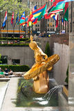 Side view of the sculpture of Prometheus in Rockefeller Center in Midtown Manhattan, New York, USA. New York, USA, May 7, 2013: Prometheus monument and flags on Stock Photo