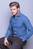 Side view of a seated young fashion man Royalty Free Stock Image