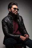 Side view of a seated young man in leather jacket and sunglasses Royalty Free Stock Photo