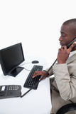 Side view of a secretary answering the phone while using a compu Royalty Free Stock Photos