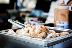Donuts in selective focus with tongs and toppings Doughnuts Stock Images