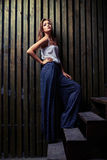 Side view of self-confident young lady leaning on wooden wall wh Stock Photography