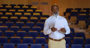 African American businessman practicing speech in empty auditorium 4k. Side view of senior African American businessman practicing speech in empty auditorium. He stock footage
