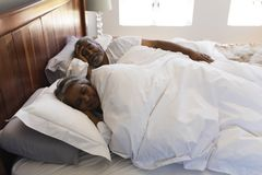 Senior couple sleeping in bedroom at home stock images