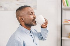 Side view of senior african american man. Drinking coffee at home royalty free stock photography