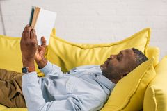 Side view of senior african american man. Lying on couch and reading book royalty free stock photo