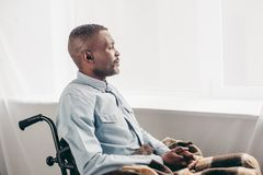 Side view of senior african american man. Sitting in wheelchair and looking away royalty free stock photos