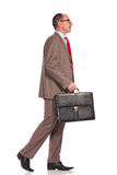 Side view of a senior businessman holding suitcase and walking Stock Photo