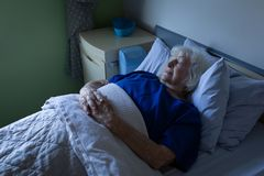 Senior female patient sleeping in a hospital bed. Side view of a senior Caucasian female patient sleeping with hands joined in a hospital bed at hospital royalty free stock images