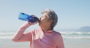 Senior woman drinking water on the beach