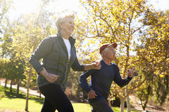 Side View Of Senior Couple Power Walking Through Park stock image