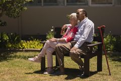 Side view of senior couple relaxing on bench in garden stock photography