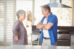 Side view of senior couple talking in kitchen Royalty Free Stock Photo