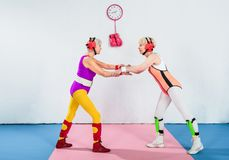 Side view of senior female wrestlers in head protection fighting and looking. At each other royalty free stock image