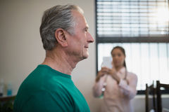 Side view of senior male patient with female therapist photographing against window Stock Photography