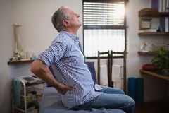 Side view of senior male patient suffering from back ache while looking up on bed Stock Photo
