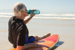 Side view of senior man drinking water while sitting on surfboard. At beach Royalty Free Stock Image