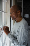 Side view of senior man looking out through window Stock Photography